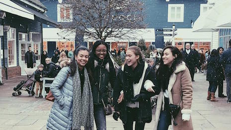 Shoppers at England's Bicester Village outlet mall posing in front of the Gucci store. Image credit: Bicester Village