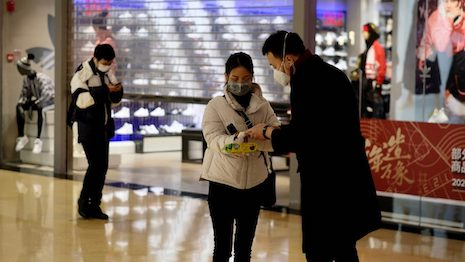 Shopping mall staff checking the temperature of customers. Image credit: Shutterstock