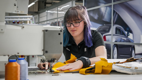 Apprentice Anna Flynn stitching seats for a Rolls-Royce car. Image courtesy of Rolls-Royce Motor Cars