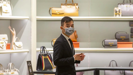 Sign of the times: Masked employee in a luxury store