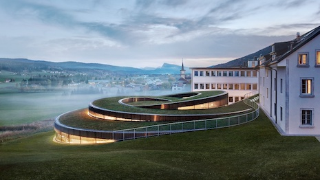 The Musée Atelier Audemars Piguet in Le Brassus unifies the original workshop created by Audemars Piguet's founders in 1875 with a new glass structure that is made up of two spirals that integrate into the landscape. Image courtesy of Audemars Piguet
