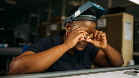 Employee sorting through rough diamonds with loupe. Image courtesy of GSS Botswana